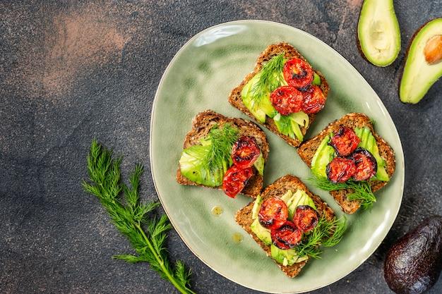 Tostadas de aguacate con tomates asados en un plato