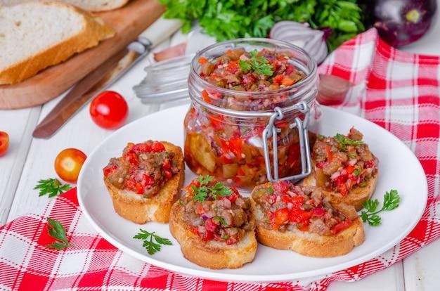 Tostadas crujientes con caviar de berenjena en un plato blanco