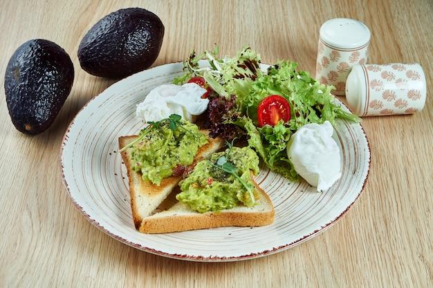Tostadas (crutones) con guacamole de aguacate servido con huevos escalfados y lechuga en un plato blanco de cerámica sobre una mesa de madera. cocina mexicana moderna. vista cercana de comida sabrosa