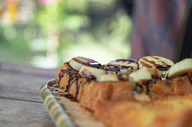 Tostadas cubiertas con plátano, choques de chocolate. madera puesta en un plato clásico.