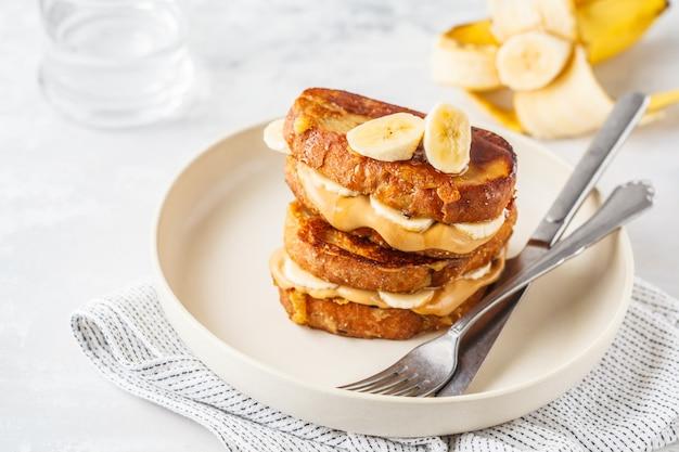 Tostadas francesas con mantequilla de cacahuete y plátano en una placa blanca.