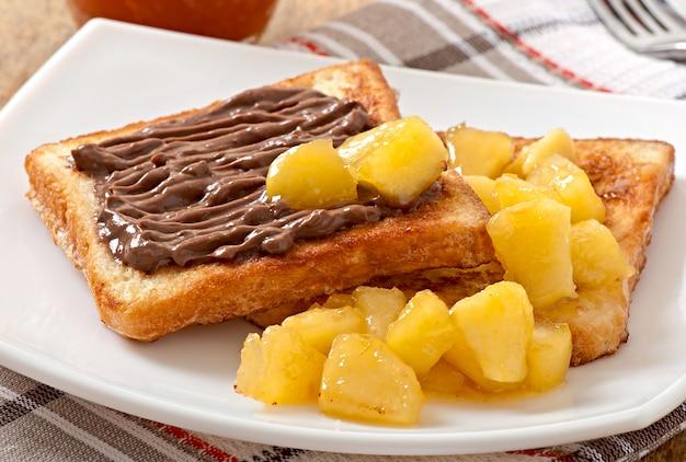 Tostadas francesas con manzanas caramelizadas y crema de chocolate para el desayuno.
