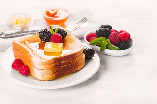 Tostadas francesas con miel, mantequilla y bayas frescas.