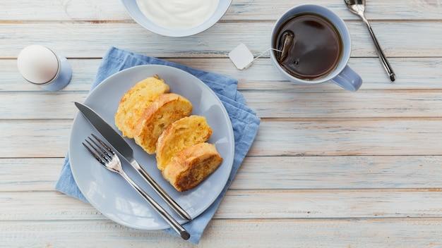 Tostadas fritas con té, huevos duros y yogur fresco, sabroso desayuno de granjero