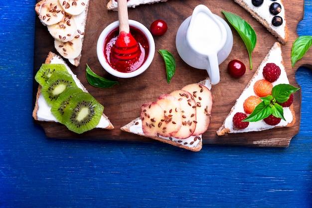 Tostadas de frutas sobre tabla de madera sobre fondo azul rústico