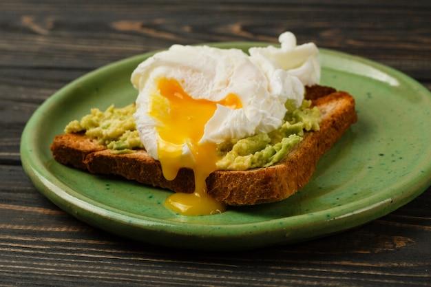 Tostadas y huevo escalfado con aguacate en un plato verde en mesa de madera