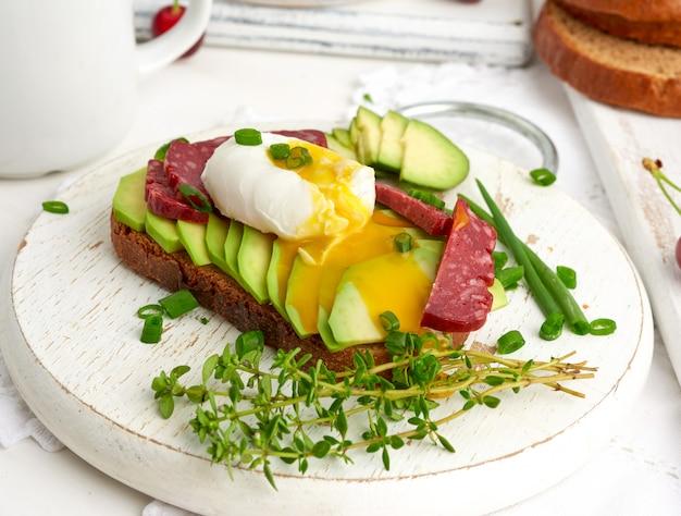 Tostadas con huevo escalfado y aguacate en una tabla redonda, desayuno por la mañana