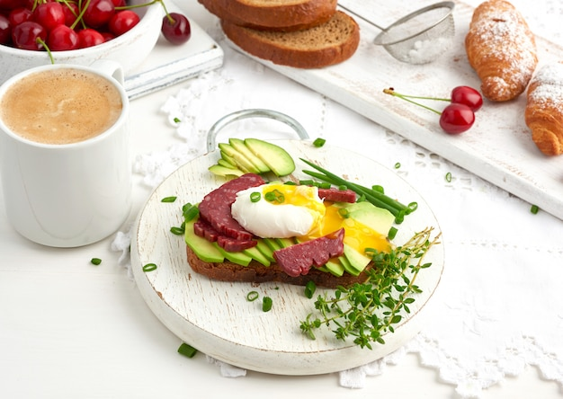 Tostadas con huevo escalfado y aguacate en una tabla redonda, junto a croissants y cerezas rojas maduras, desayuno, vista superior sobre una mesa blanca