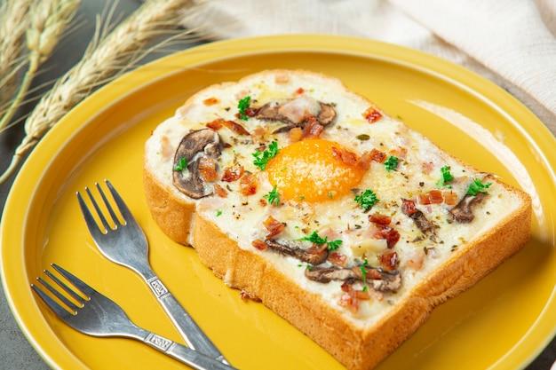 Tostadas con huevo frito y queso crema sobre fondo oscuro