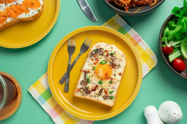 Tostadas con huevo frito y queso crema sobre fondo verde pastel