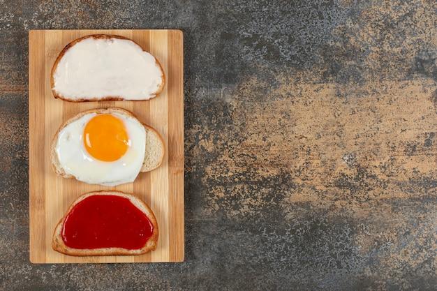 Tostadas con huevo, queso crema y mermelada sobre tabla de madera.