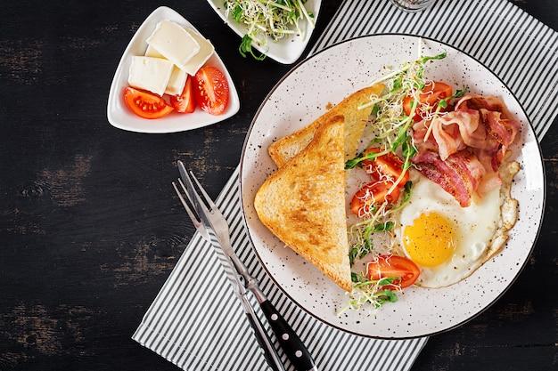 Tostadas, huevo, tocino y ensalada de tomates y microgreens.