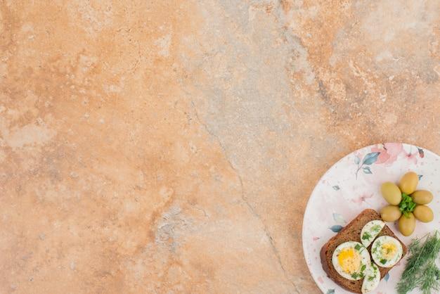 Tostadas con huevos duros en mesa de mármol