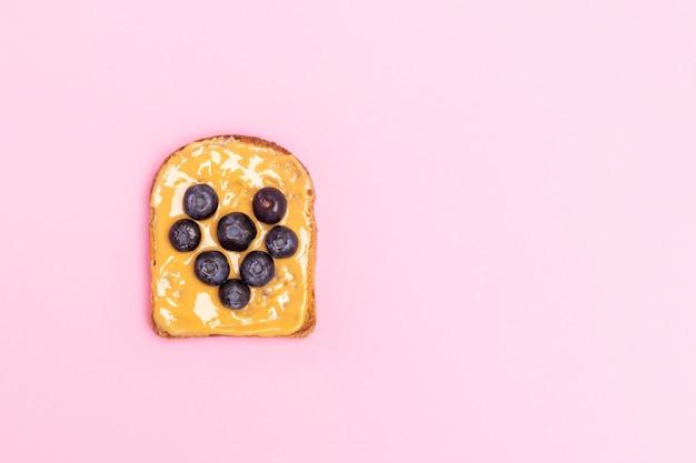 Tostadas de mantequilla de maní con arándanos en forma de corazón para el desayuno sobre fondo rosa pastel con espacio de copia