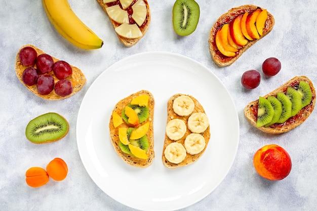 Tostadas con mantequilla de maní, mermelada de fresa, plátano, uvas, melocotón, kiwi, piña, frutos secos