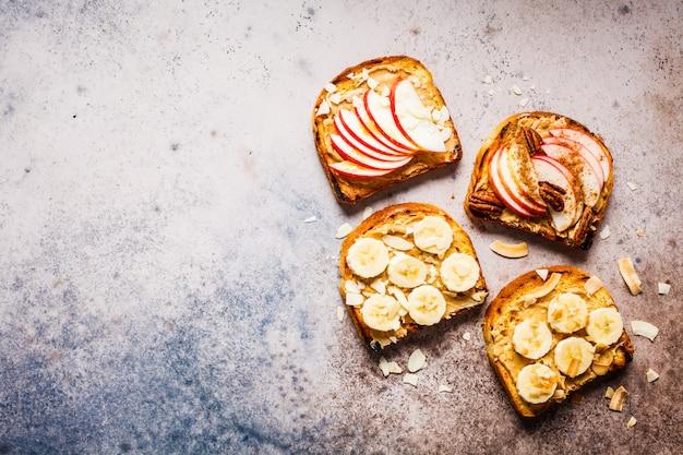 Tostadas de mantequilla de maní con plátano y manzana sobre un fondo gris, endecha plana.