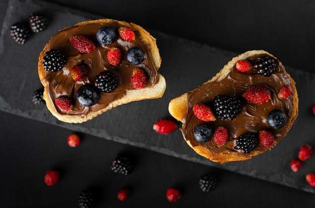 Tostadas con mantequilla de nuez de chocolate con bayas silvestres frescas sobre fondo oscuro