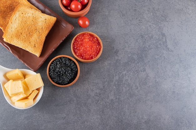 Tostadas con mantequilla y tomates cherry rojos colocados sobre fondo de mármol.