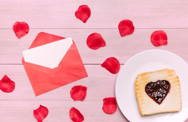 Tostadas con mermelada en forma de corazón con pétalos de rosas.