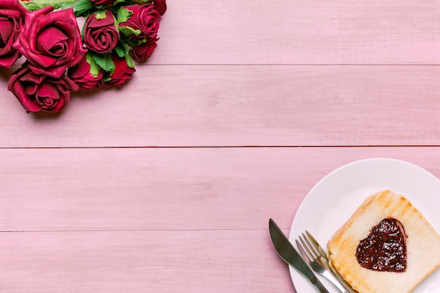 Tostadas con mermelada en forma de corazón con rosas rojas.