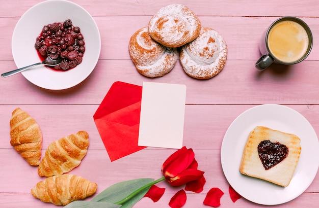 Tostadas con mermelada en forma de corazón con tulipanes, bayas y papel en blanco