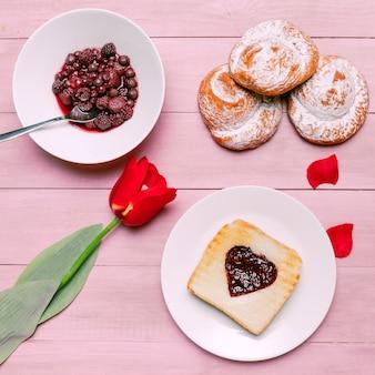 Tostadas con mermelada en forma de corazón con tulipanes y bayas.