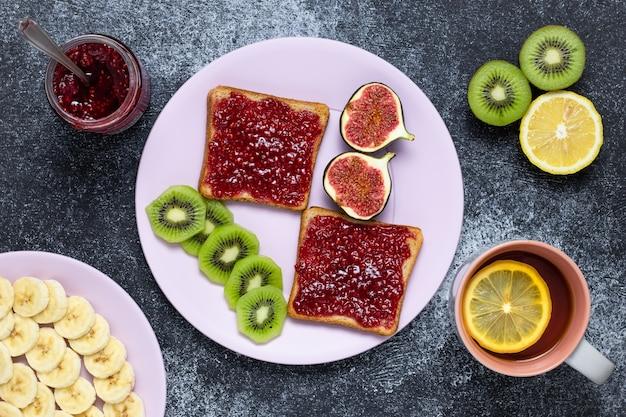 Tostadas con mermelada de frambuesa, té de limón y frutas