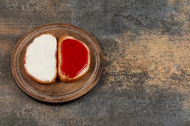 Tostadas con mermelada de fresa y crema agria sobre tabla de madera.