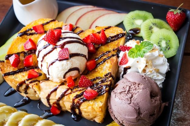 Tostadas de miel. postre dulce servido con fruta variada y helado.