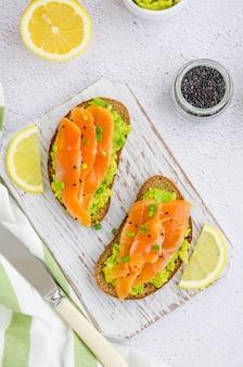Tostadas de pan de centeno, aguacate, salmón ahumado, cebollas verdes y semillas de sésamo.