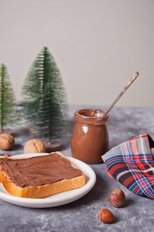 Tostadas de pan con mantequilla de crema de chocolate con juguetes de árbol de navidad