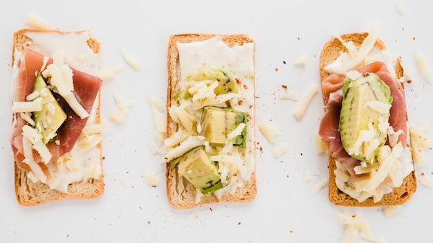 Tostadas de pan con queso rallado; loncha de jamón y aguacate sobre fondo blanco