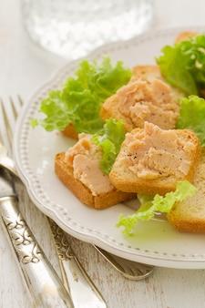 Tostadas con paté de pescado en un plato blanco sobre fondo blanco.