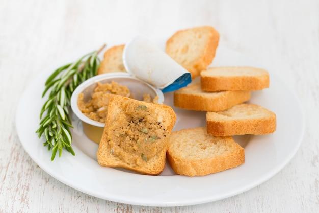 Tostadas con paté de pescado en plato blanco