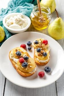 Tostadas con pera, queso crema, nueces y miel.