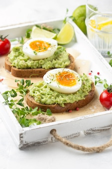 Tostadas con puré de aguacate y huevo pasado por agua en una bandeja blanca, yema líquida, delicioso desayuno, sándwich ligero