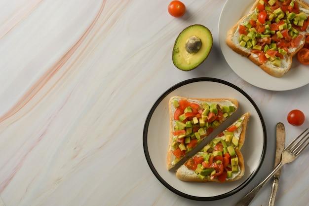 Tostadas con queso crema, aguacate y tomates cherry. comida sana. copia espacio