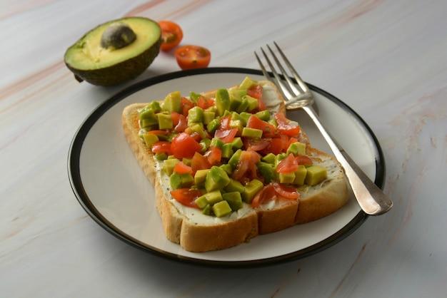 Tostadas con queso crema, aguacate y tomates cherry. comida sana.