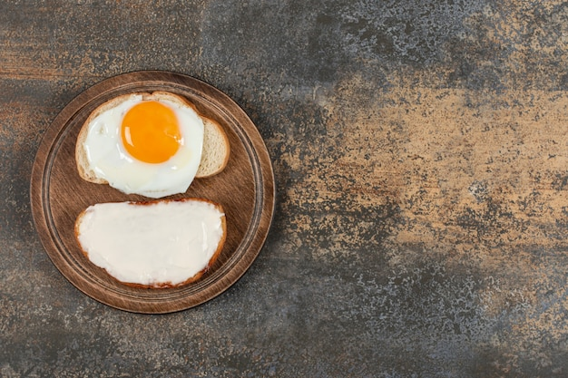 Tostadas con queso crema y huevo sobre tabla de madera.