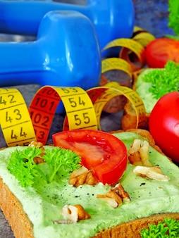 Tostadas con requesón verde y nueces y tomate. cinta métrica. mancuernas comida de fitness.