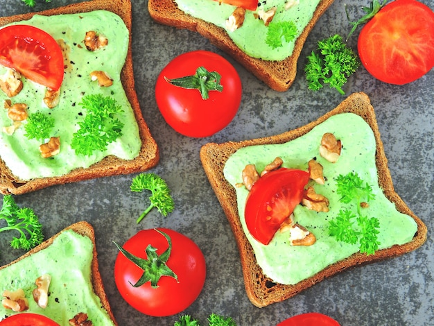 Tostadas con requesón verde, nueces y tomates. tostadas de centeno. el concepto de una merienda útil.