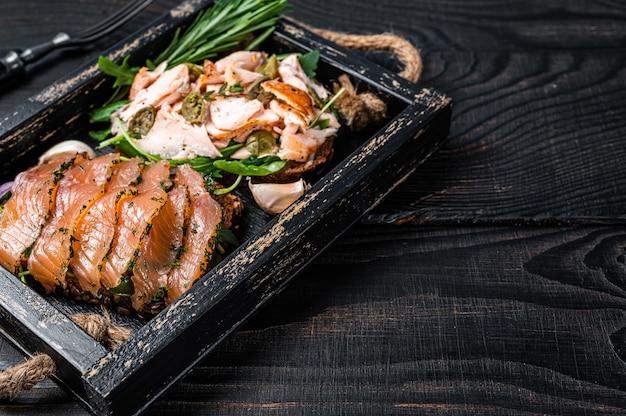 Tostadas con salmón ahumado frío y caliente, rúcula en bandeja de madera con hierbas