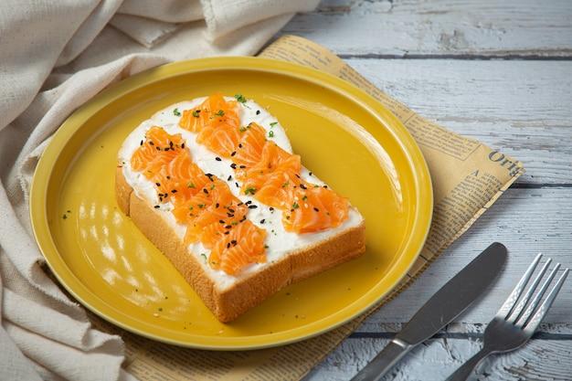 Tostadas con salmón ahumado y queso crema sobre mesa de madera