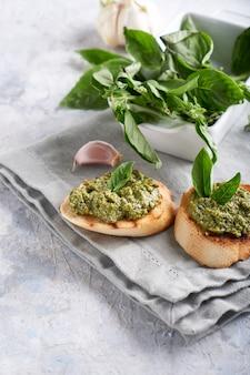 Tostadas con salsa tradicional italiana de pesto de albahaca sobre una mesa de piedra clara