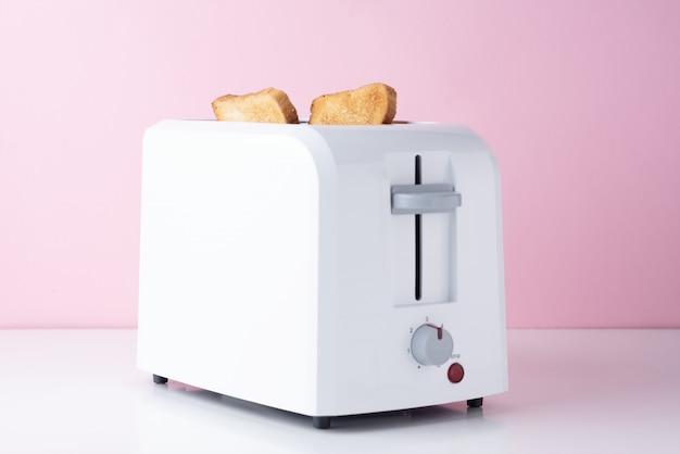 Tostadora blanca con pan tostado tostado sobre fondo rosa, de cerca
