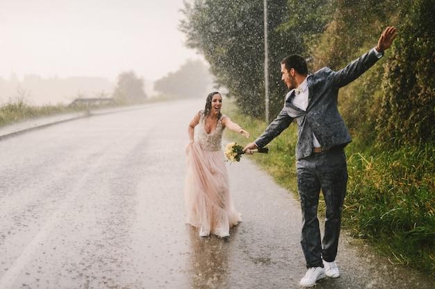 Totalmente mojado pareja de recién casados caminando bajo la lluvia por carretera
