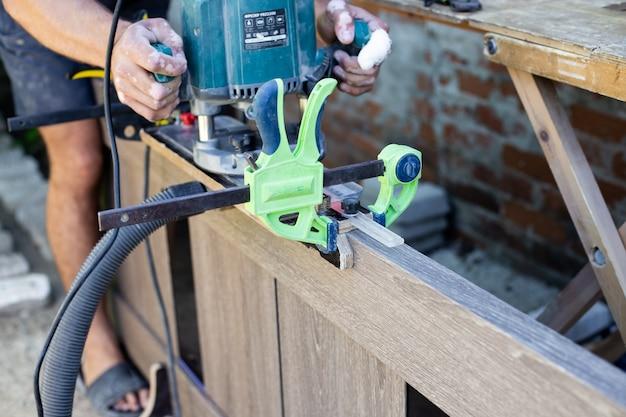Trabaja densamente con una fresadora en la superficie de madera de la puerta. herramientas profesionales para trabajar la madera.