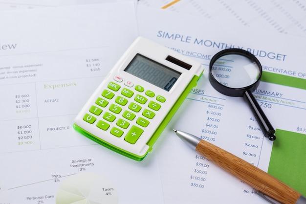 Trabaja con una lupa, una calculadora y papeles.