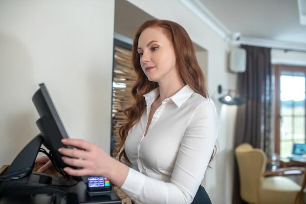 Trabaja. mujer adulta joven con el pelo largo de jengibre en blusa blanca de pie en la habitación tocando el monitor con la mano