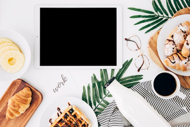Trabaja texto en papel cerca de la tableta digital; rodajas de piña; cuerno; waffles botella; taza de café y anteojos en escritorio blanco